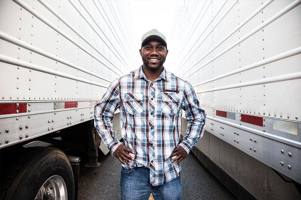 Trucker standing by his large truck