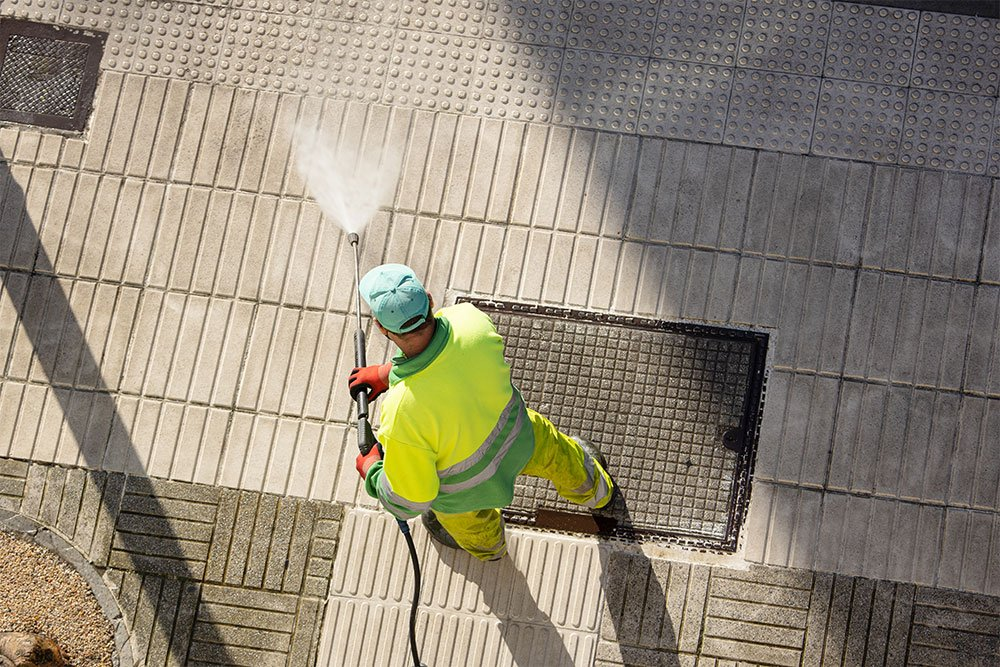 worker cleaning a street sidewalk with high pressure