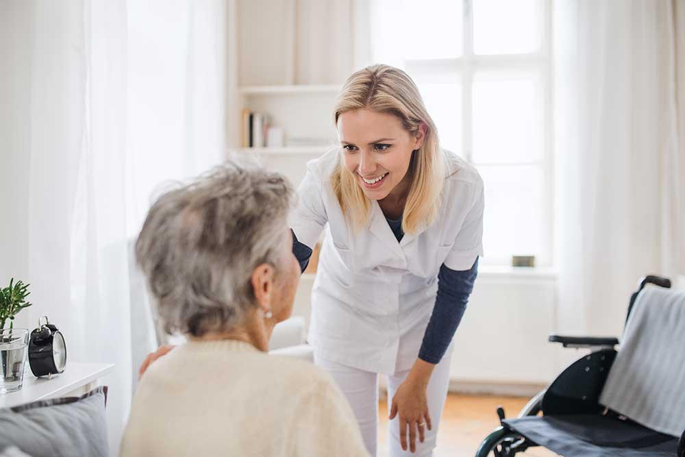 a health visitor talking to a senior woman sitting