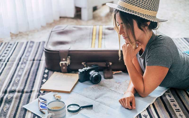 caucasian-woman-planning-vacation-travel-with-map